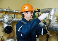 Thermal insulation. worker insulating heating system pipes with foil Royalty Free Stock Photography