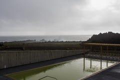 Thermal pool and atlantic ocean in Volcanic coastline. Stunning landscape of Volcanic coastline Ponta da Ferraria in Azores royalty free stock images