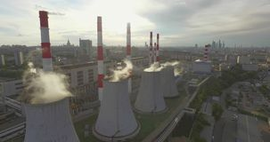 Thermal Power Plant. Aerial 4K shot of smoke or steam coming from an industrial chimney, Thermal power plant with huge cooling towers in city suburbs. Industry stock video