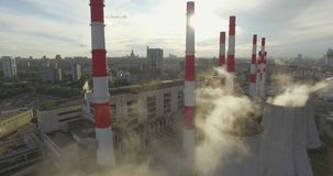 Thermal Power Plant. Aerial 4K shot of smoke or steam coming from an industrial chimney, Thermal power plant with huge cooling towers in city suburbs. Industry stock footage