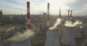Thermal Power Plant. Aerial 4K shot of smoke or steam coming from an industrial chimney, Thermal power plant with huge cooling towers in city suburbs. Industry stock video footage