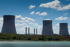 Thermal power plant chimneys near lake stock photo