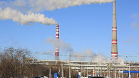 Thermal power plant in sunny cold day. Industrial smoke from the pipes against blue sky. stock video footage