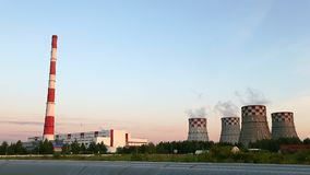 Thermal Power Station edge of city summer evening dolly shot. Smoke go up to blue sky. Energy production and pollution. This is a modern urban landscape stock video footage