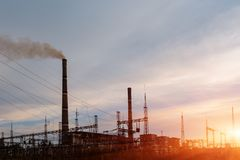 Thermal power stations and power lines during sunset. Stock Photo