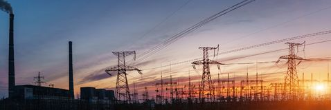 Thermal power stations and power lines during sunset. Thermal power plant with tubes and high-voltage power lines at sunset Royalty Free Stock Photos