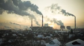 Thermal station smoke in sky at winter sunset Royalty Free Stock Photo
