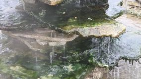 Thermal water flowing over rocks stock video