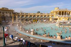 Thermalen badar Széchenyi i öppen luft med avslappnande folk på solig dag Berömda ungerska brunnsortbad Arkivbild