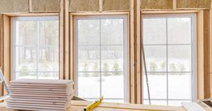 Thermally insulating eco-wood frame house with wood fiber plates and heat-isolating natural hemp material. Finishing the. Walls and a large window with a white stock photo