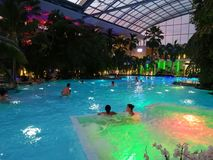 Therme Bucharest, Palm Zone in the night. Indoor pool with thermal water and colorful lights royalty free stock images