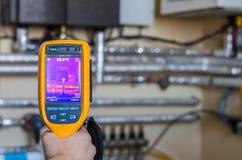 Thermische weergaveinspectie van hittesysteem met buizen bij huis Stock Afbeeldingen
