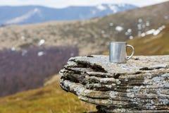 Thermo Becher des Edelstahls auf einem flachen Stein innerhalb tne Berge lizenzfreie stockfotografie