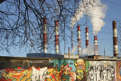 Thermoelectric power station. Electrical power station pipes. White smoke against the blue sky. Concrete fence with graffiti Royalty Free Stock Images