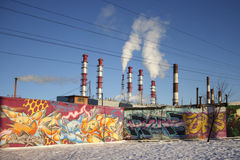 Thermoelectric power station. Electrical power station pipes. White smoke against the blue sky. Concrete fence with graffiti Stock Photography
