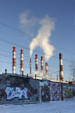 Thermoelectric power station. Electrical power station pipes. White smoke against the blue sky. Concrete fence with graffiti Stock Photos