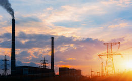 Thermoelectric station generanting smokes at the sunset. Stock Photos