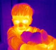 Thermograph-Boy with teddy. A cute child embracing his teddy bear. Real infrared (thermic) photo in blue Royalty Free Stock Photo