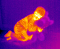 Thermograph-Kid and teddy. A cute child with his teddy bear. Real infrared (thermic) photo in blue Royalty Free Stock Image
