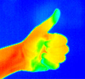 Thermograph-Thumb up 2. Real infrared (thermic) photo of a thumb up with blue background Royalty Free Stock Photography