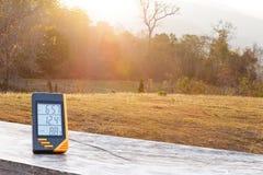 Thermomètre d'affichage numérique avec l'herbe et la lumière du soleil Images libres de droits