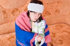 Thermomètre de fille sur le divan Image stock