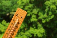 Thermomètre en bois à la lumière du soleil d'été montrant la haute température photo stock