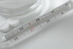 Thermomètre et comprimés de photo de foyer sélectif Image stock