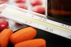 Thermomètre et médicament Photographie stock libre de droits