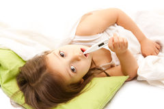 With thermometer. Illness little girl on bed Stock Photos