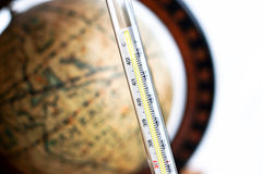 Thermometer with antique globe background Royalty Free Stock Photo