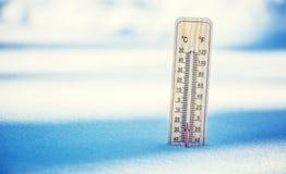 Thermometer auf Schnee zeigt niedrige Temperaturen unter null Niedrige Temperaturen in den Grad Celsius und Fahrenheit Stockfotografie