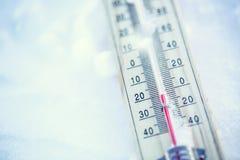 Thermometer auf Schnee zeigt niedrige Temperaturen unter null Niedrige Temperaturen in den Grad Celsius und Fahrenheit Lizenzfreie Stockfotografie