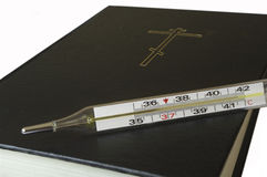 Thermometer and the Bible. Royalty Free Stock Photos