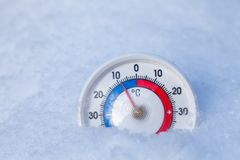 Snowed thermometer shows minus 9 Celsius degree cold winter weather concept. Thermometer with celsius scale placed in a fresh snow showing sub-zero temperature royalty free stock photos