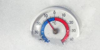 Outdoor thermometer in the snow shows decreasing temperature - cold winter weather change concept stock footage