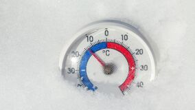 Outdoor thermometer in the snow shows increasing temperature - spring warming weather concept. Thermometer with Celsius scale placed in snow showing temperature stock video footage