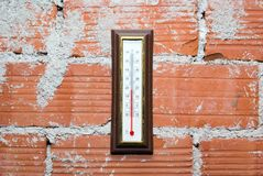 Thermometer, der an der roten Backsteinmauer hängt Lizenzfreies Stockfoto