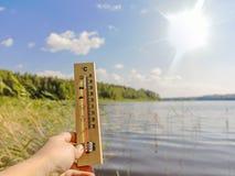 Thermometer die 30 graden van Celsius tonen van hitte tegen de achtergrond van het meerwater en de blauwe hemel in zonlicht royalty-vrije stock foto