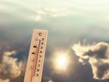 Thermometer die 30 graden van hitte tonen tegen de achtergrond van meerwater met de bezinning van wolken en de zon stock afbeeldingen