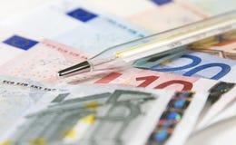 Thermometer en gezondheidszorgfinanciën Stock Foto's