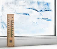 Thermometer on a frozen window and cold weather Stock Photos