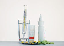 Thermometer in a glass of water and medication for the table Royalty Free Stock Photo