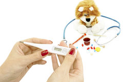 Thermometer in hand and soft toy with a stethoscope Stock Photography