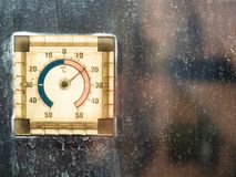 Thermometer illuminated by sun on dirty window stock image