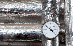 Thermometer isolated pipes. A thermometer mounted on some temperature-isolated pipes stock photos