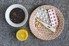 Thermometer, jam, citroen, tabletten voor koude op grijze backgroun Stock Foto's