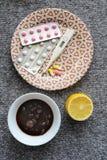 Thermometer, jam, citroen, tabletten voor koude op grijze backgroun Stock Foto