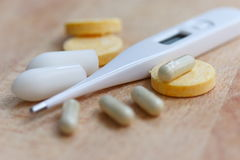 Thermometer and pills. An electronic thermometer with some pills and suppositories on a wooden surface Stock Images