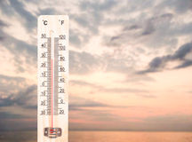 Thermometer on ocean or sea sunset background Stock Photos